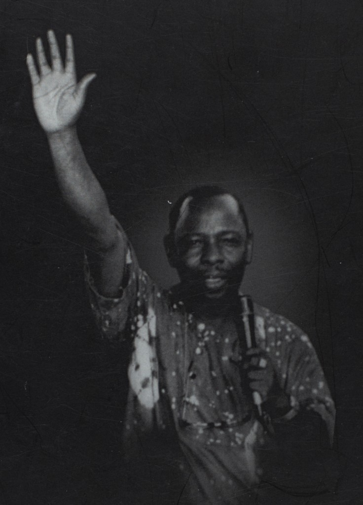 Ken Saro-Wiwa holding up one hand, the other holding a mic